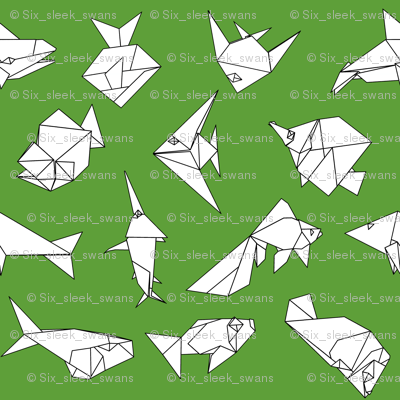 Origami fish folds on green