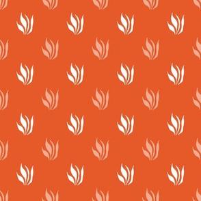 White plant leaves on orange background