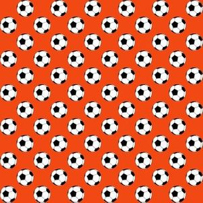Half Inch Black and White Sports Soccer Balls on Red-Orange