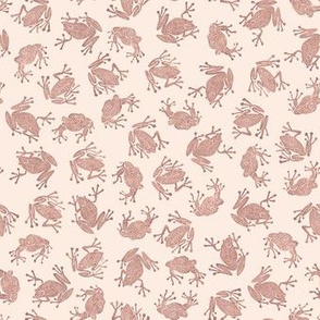 small terracotta frogs on pale pink