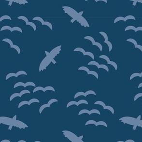 Flying birds. Bird silhouettes light blue on a dark blue background. Flock of birds. Swarm of birds.