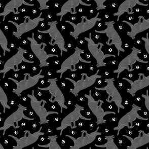 Trotting black German Shepherd dogs and paw prints - black