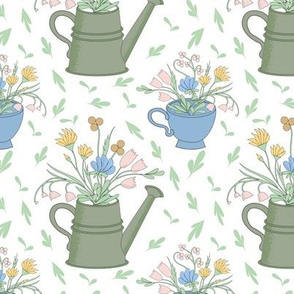 wild flowers in watering cans and cups