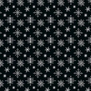 White hand-drawn snowflakes on black