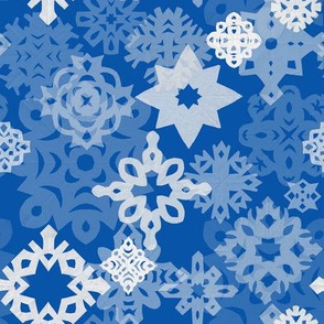 Paper snowflakes and stars on indigo background