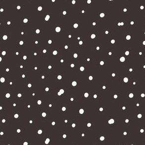 White hand drawn polka dot on brown background.