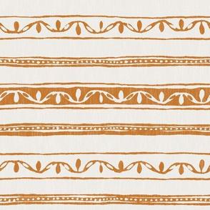 small ornaments in ochre on cream linen