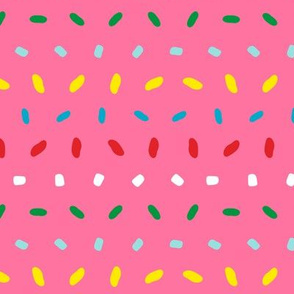 Shimmering colorful sprinkles pattern aligned on pink background