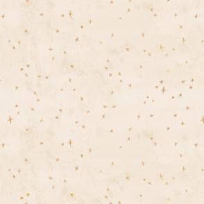 Scattered gold metallic stars on cream texture