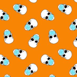 skulls in medical masks on orange