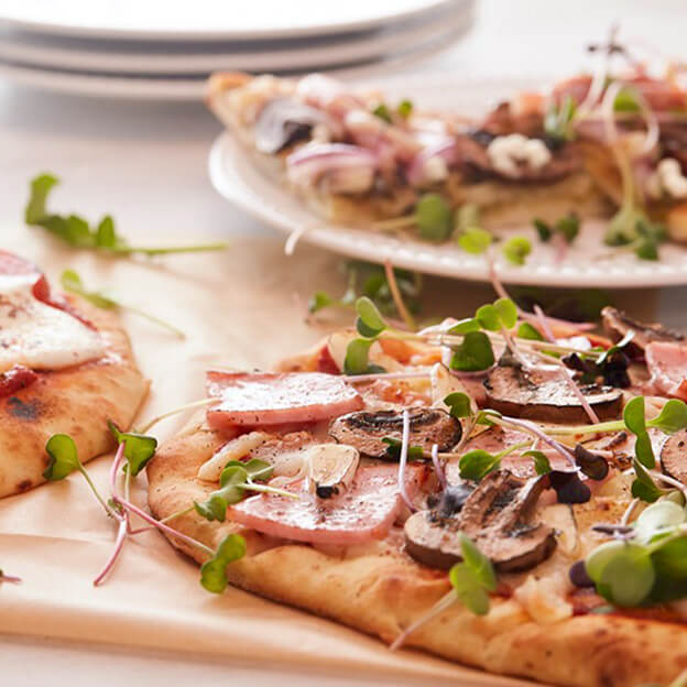 Three pizzas with Square Roots Roots' microgreens and arugula