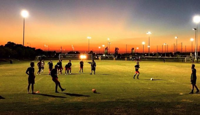 houston express players on a soccer field at dusk