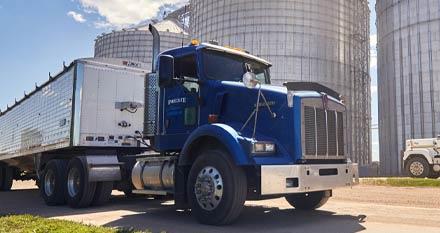 Semi Truck infront of silos.