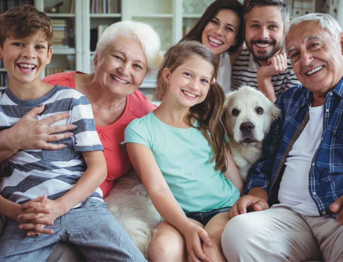 Multi-generational family with golden retriever on couch.