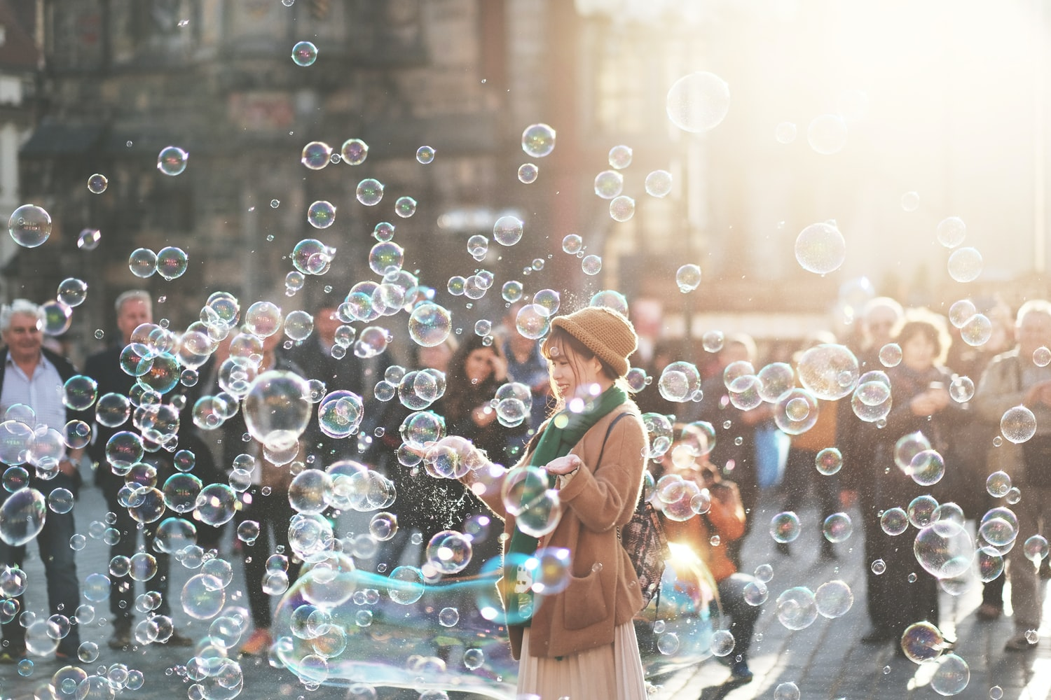 Woman blowing soap bubbles on a busy street