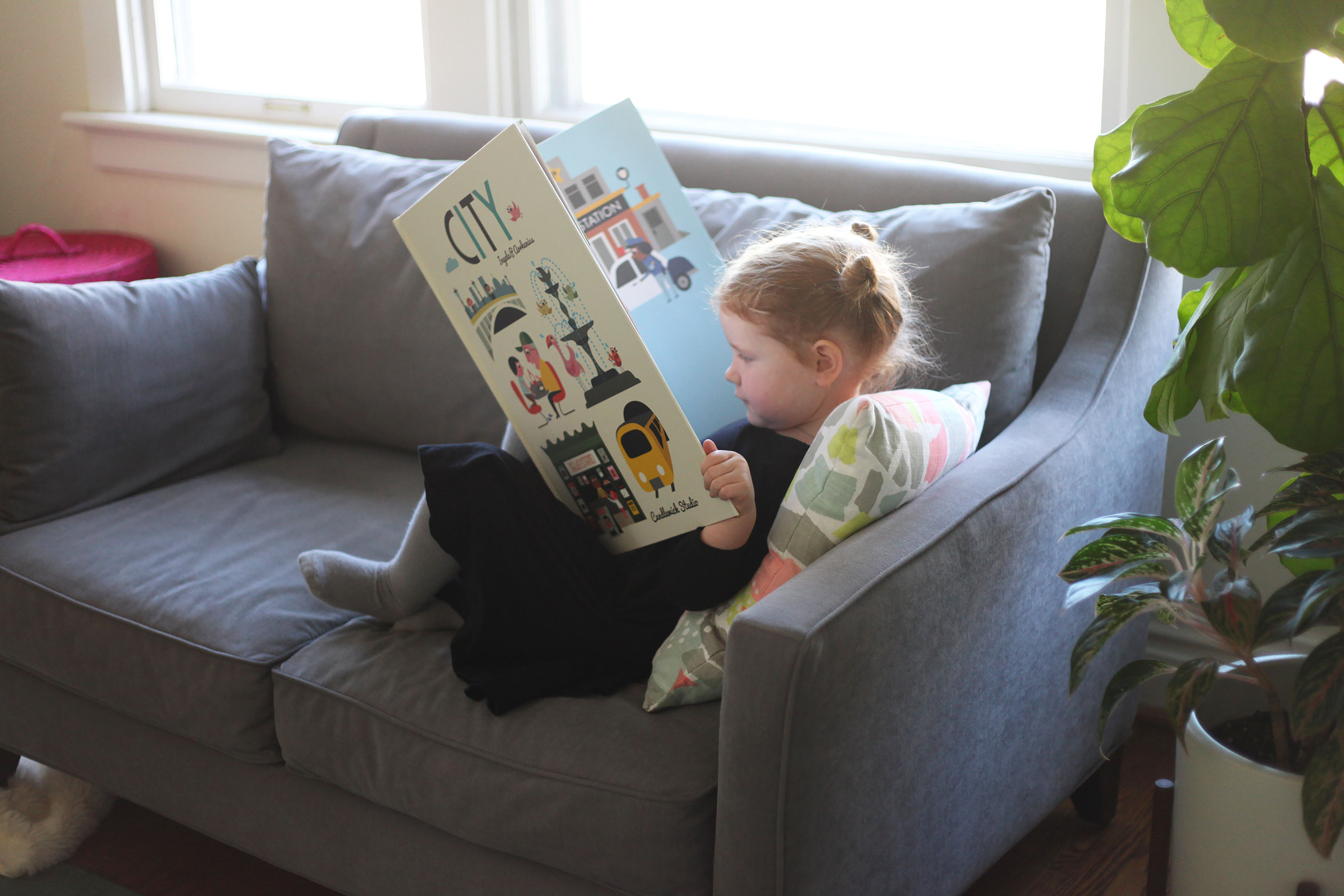Child-Reading-Oversize-Book-On-Couch