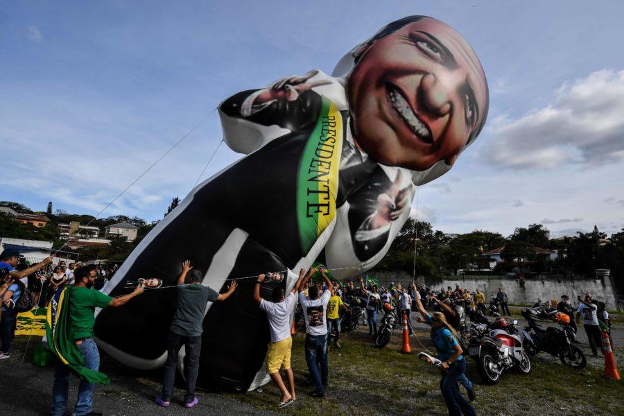 Apoiadores de Bolsonaro levantam um balão com o candidato com a faixa presidencial.