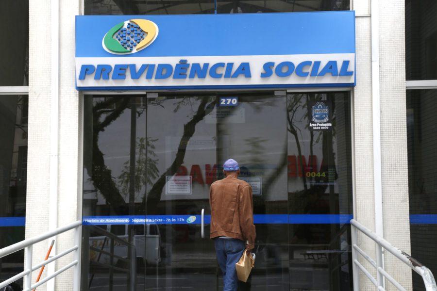 Fachada de agência do INSS, com a logo Previdência Social na entrada.
