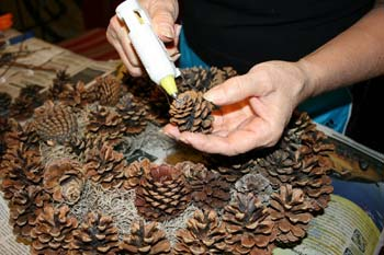 gluing pinecones to a wreath