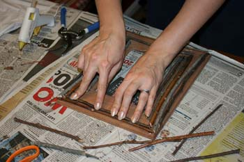 Press and hold twigs firmly in place as glue sets them to the frame