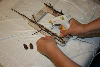 Decorate the decoupage frame with twigs, nuts, pinecones et al.