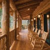 Large-diameter logs support the front porch. Lantern-style lights flank aluminum-clad patio doors. Rustic pine rockers afford comfort while viewing the surrounding mountains.