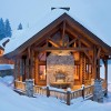 On a snowy winter's night, a blazing fire warms the cabin's outdoor area. The double-sided fireplace serves both the great room inside and this sheltered outdoor space.