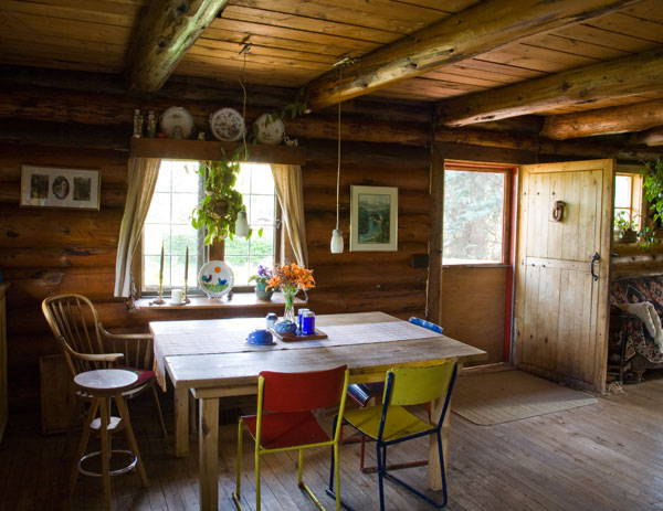 """The Ewerts relied only on local, natural materials to build and maintain their two-story three-bedroom cabin. """"We like the look of old-fashioned oiled logs, and we didn't want to use any chemical preservatives,"""" Linda says. """"We just wipe them down with linseed oil every year."""""""