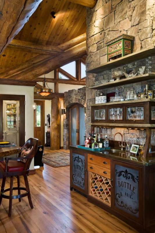 A wet bar was built into the back of the floor-to-ceiling fireplace. Featuring cut stone storage ledges, the piece also incorporates a saloon-style zinc countertop and sink. An arched stone-face closet flanks the home's main entry. Wavy willow branches are embedded in its frosted glass doors.