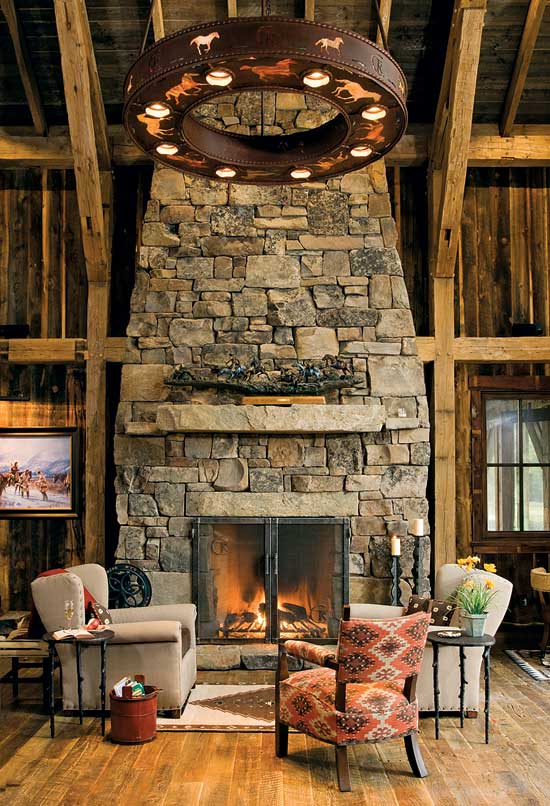 The stunning stacked-stone fireplace creates an instant focal point in this 850-square-foot Montana timber frame. Photo by Heidi Long.
