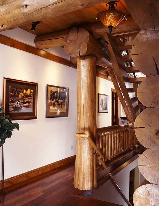 Brian's collection of Western art is showcased in the hallway that transitioned the great room to the stairs leading to the loft and lower level. Pioneer's Alaskan staggered-tail support posts and beams with exposed roots lend an organic feel to the home. Brian sourced the bark beetle killed pine from Hester's, a local sawmill, which his crew from Mountain Log Homes of Colorado then fashioned all of the 'beefy' railings to fit the feel of a large-diameter log home.