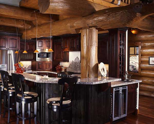 Large diameter handcrafted pine posts and beams from Pioneer Log Homes of British Columbia add visual drama to the centrally located kitchen. Retaining the natural length of the support beam allowed them to extend the loft and add a sitting area. Karen selected a burgundy stain for the custom-built knotty alder cabinets and added deep green crown molding and tongue-and-grove around the island to complement the brown logs and African cherry hardwood floor. Gray and white granite countertops, installed by Jim Stover of Breckenridge, Colorado, brighten the space by reflecting the illumination from the hanging pendant lights. Jim also fashioned the mountain-shaped backsplash.