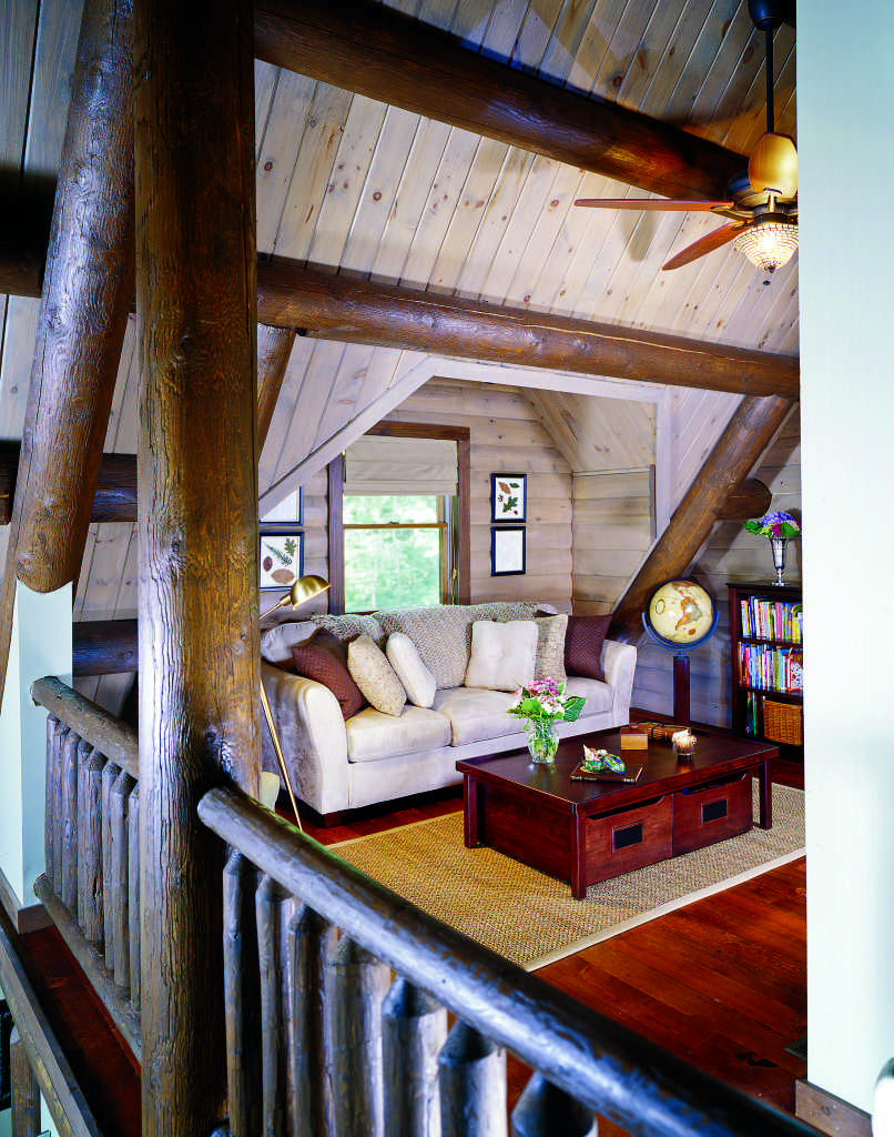 log home loft reading nook sofa coffee table sloped ceiling