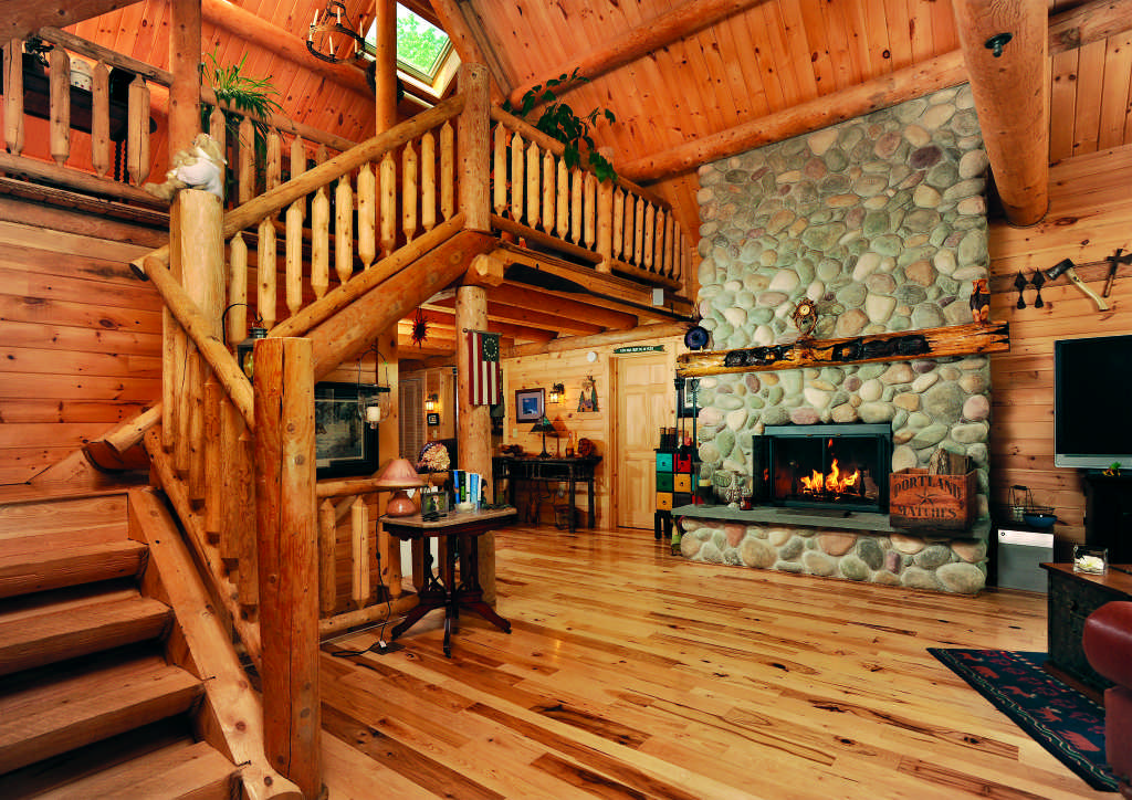 Maine log home interior staircase stone fireplace