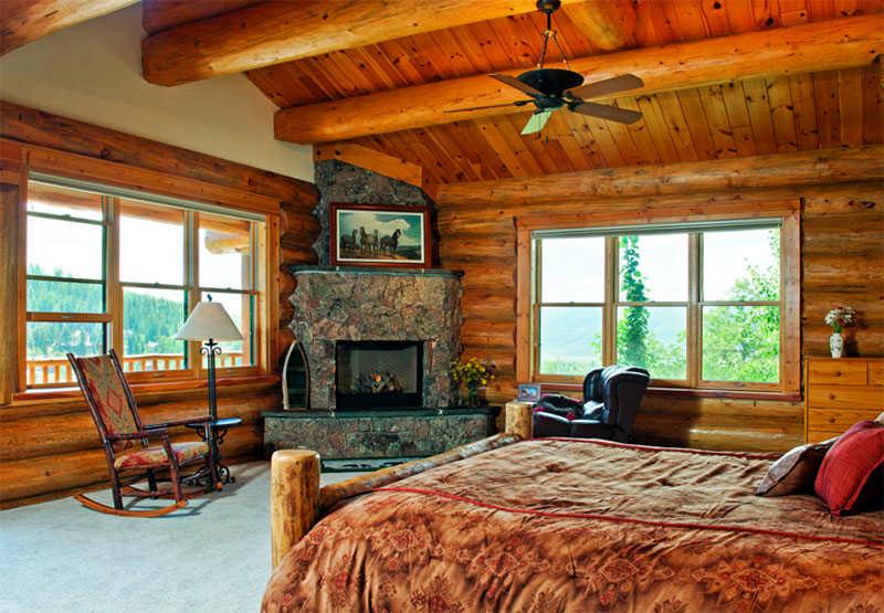 Colorado log home bedroom windows log beams stone fireplace
