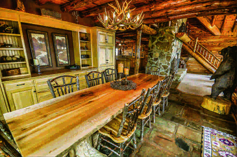 restored log home dining area with antler chandelier