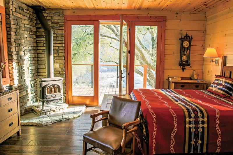 white pine log ranch bedroom wood burning stove clock deck patio stone masonry