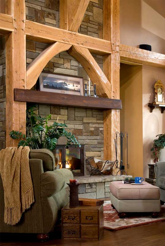 The hand-hewn timbers perfectly frame the fireplace in this cozy sitting area. Photo by Heidi Long.