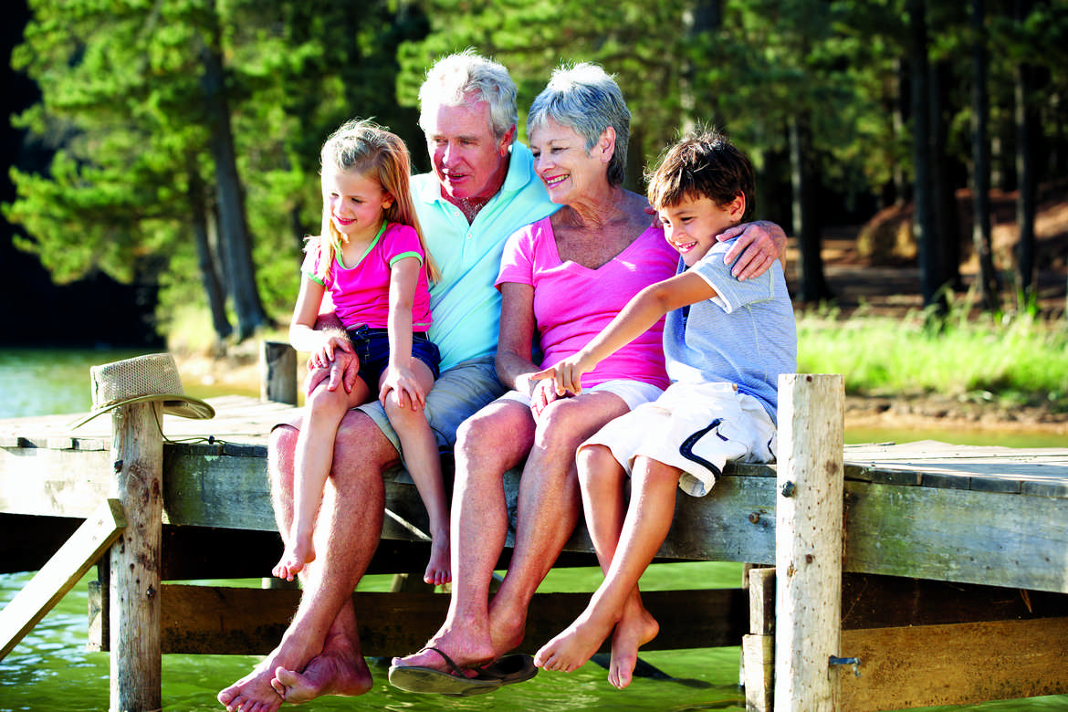 senior-couple-sitting-by-lake-with-grandchildren-2