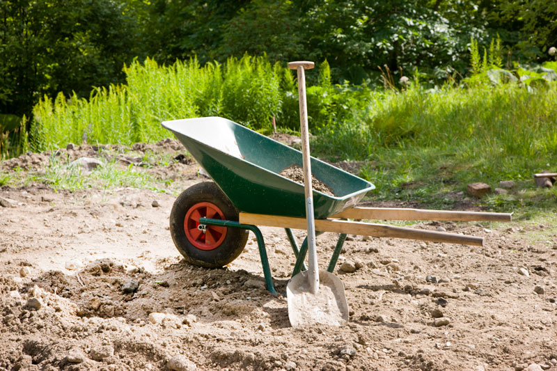 green wheelbarrow shovel dirt grass plants