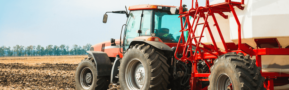 Tractor cutting crops in field