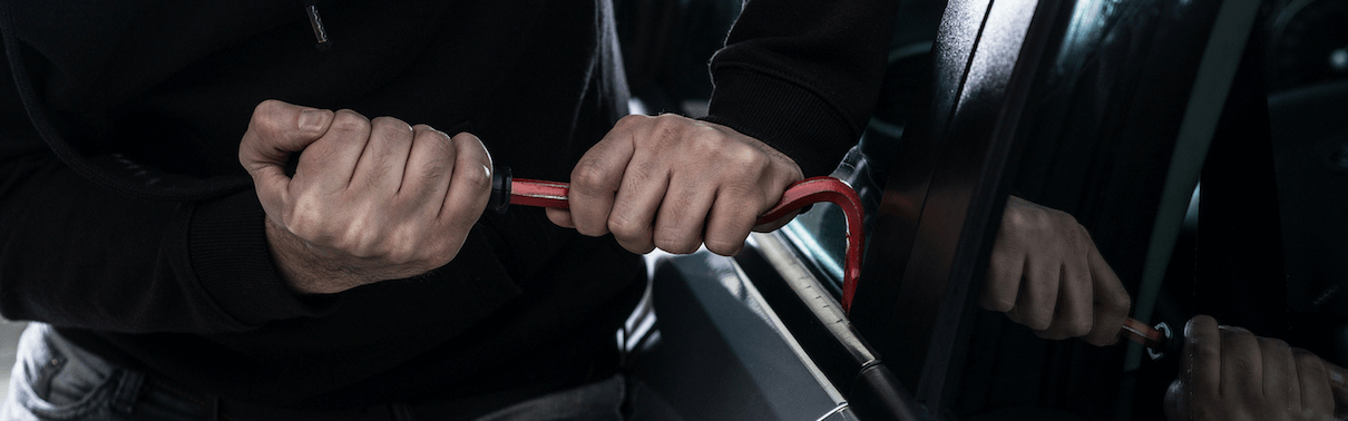 Thief trying to gain access to a vehicle using a small crowbar on the window