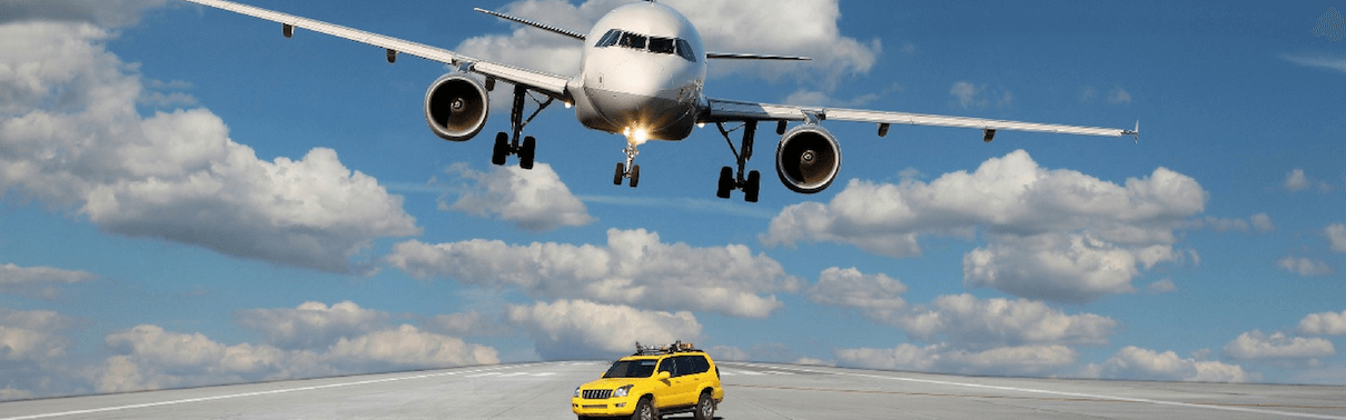 Airplane flying over vehicle on the runway
