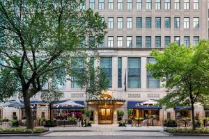 Daylight exterior view of the Sofitel Washington DC with blue awnings, patio restaurant seating, and hotel entrance.