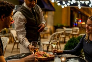 Couple seated at a bistro table enjoying wine and being served a cheese plate by a waiter at Opaline Bar in DC.
