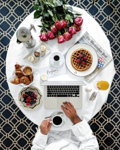 Overhead shot of marble table set with a French breakfast & a man in a robe working on a laptop
