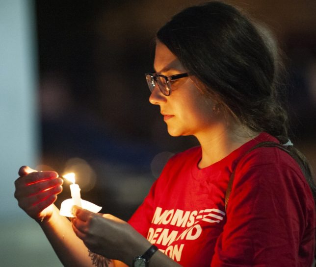 Hannah Gliemann shields her candle from the wind during an Interfaith Vigil for El Paso, Texas and Dayton, Ohio mass shooting victims hosted by the Jonesboro local group of the Arkansas Chapter of Moms Demand Action, Thursday, Aug. 8, 2019, at the Craighead County Courthouse in Jonesboro, Ark. The vigil featured speakers from several religious and non-religious groups, a 100-seconds of silence, and the lighting of candles to honor the victims of gun violence across the United States. (Quentin Winstine/The Jonesboro Sun via AP)