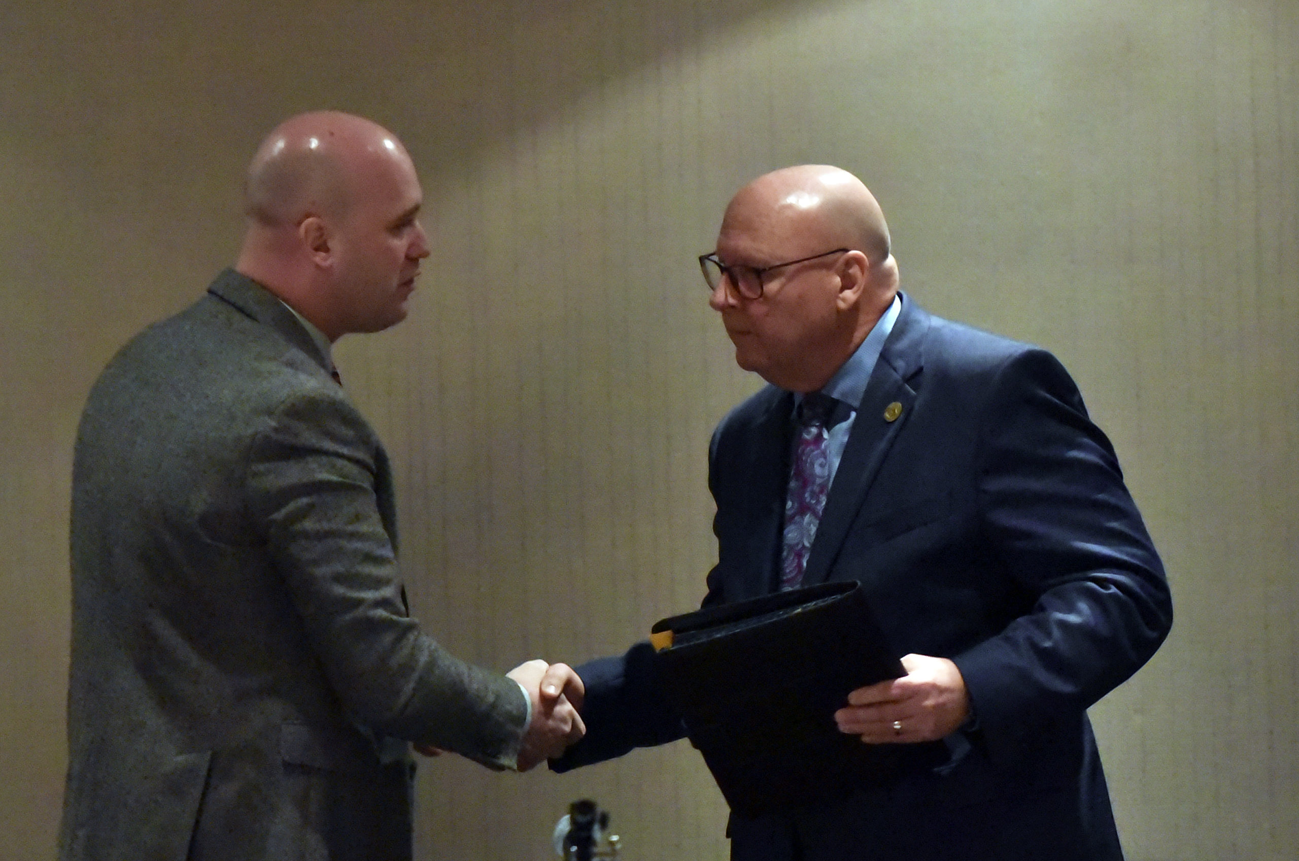 Commissioner Chairman Daniel Camp and Commissioner Jack Manning shake hands at the Annual State of the County meeting.