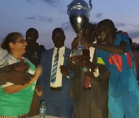 Winning team holding trophy as dusk