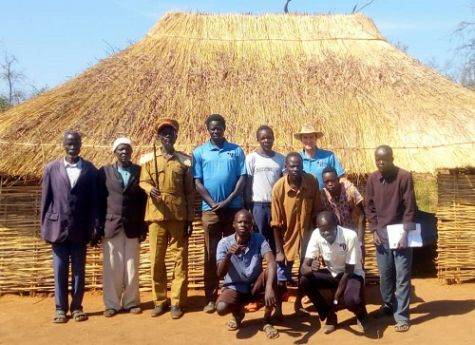 Seven elders posed in front of grass roof building in local village of Lui